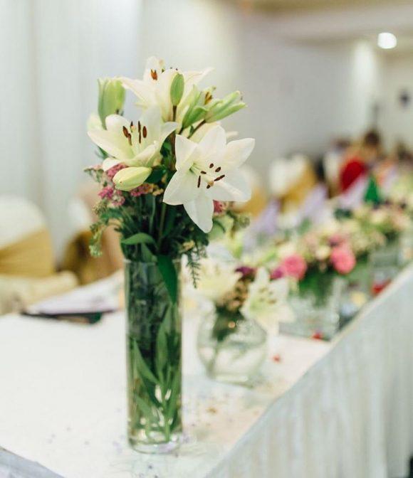 Vaza sa cvetom belog ljiljana na mladenačkom stolu