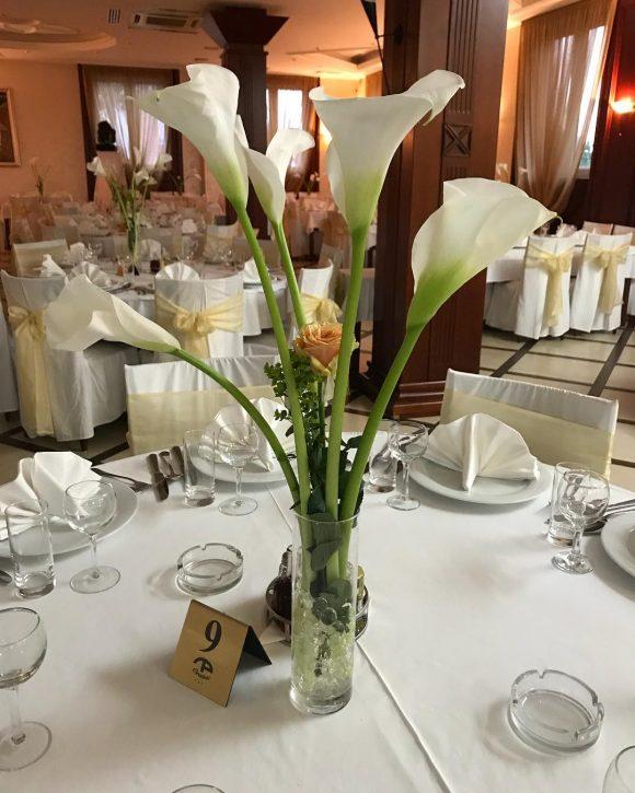 Vaza na stolu za venčanje sa belim kalama i ružom