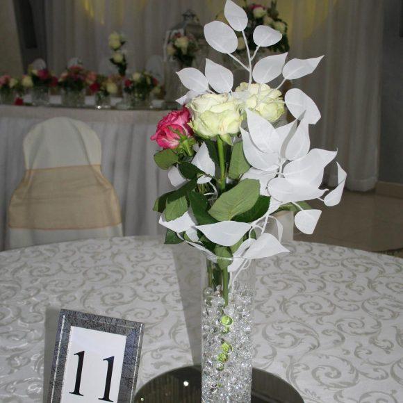 Aranžman na stolovima od belih i roze ruža u vanzni na venčanju