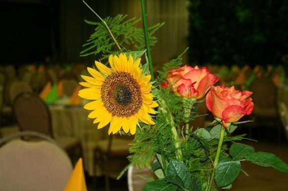 Cvetni aranžman po stolovima od ruža i suncokreta na venčanju
