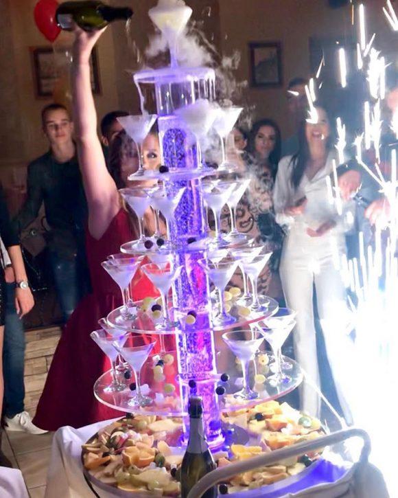 Devojka sipa šampanjac u čaše sa suvim ledom na šampanjac fontani
