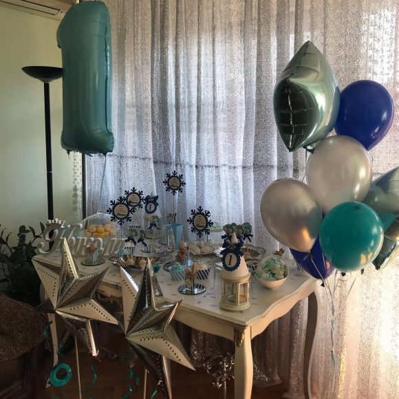 Slatki sto sa srebrnim zvezdama i helijum balonima