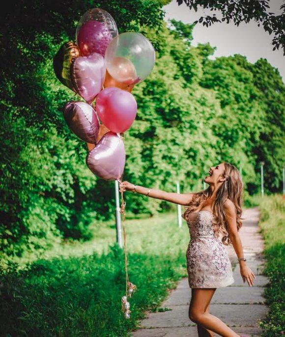Devojka drži snop sa helijum balonima