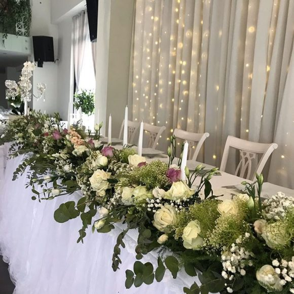 Dekoracija mladenačkog stola sa belim i roze cvećem