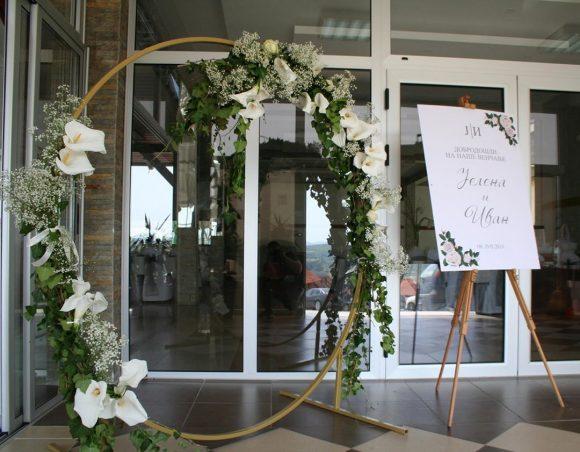 Krug za slikanje ukrašen bršljenom i cvećem kao dekoracija za venčanje