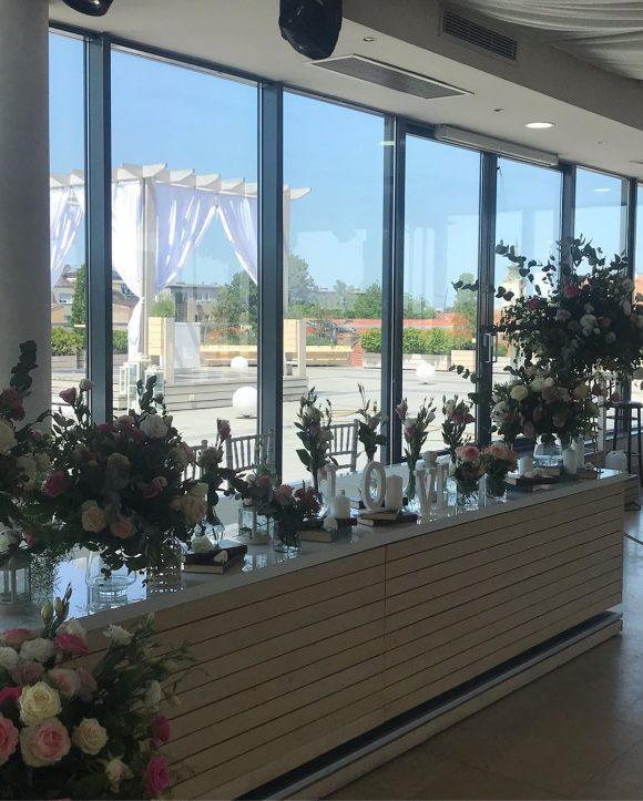 Dekoracija sa cvećem i svećama na stolu za mladence na venčanju