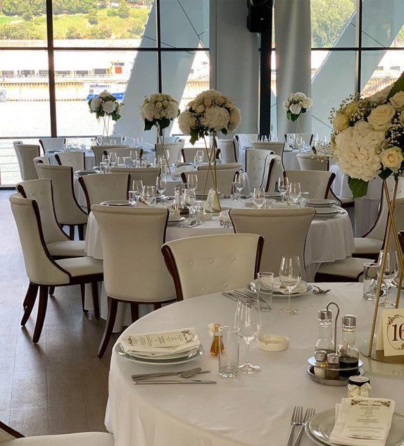 Aranžmani od belih hortenzija po stolovima dekorisani za venčanje