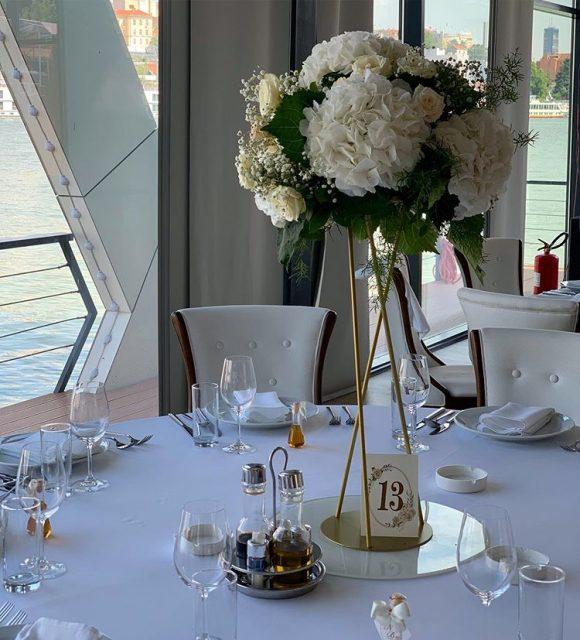 Okrugli aranžman na stolu od belih hortenzija na zlatnom postolju