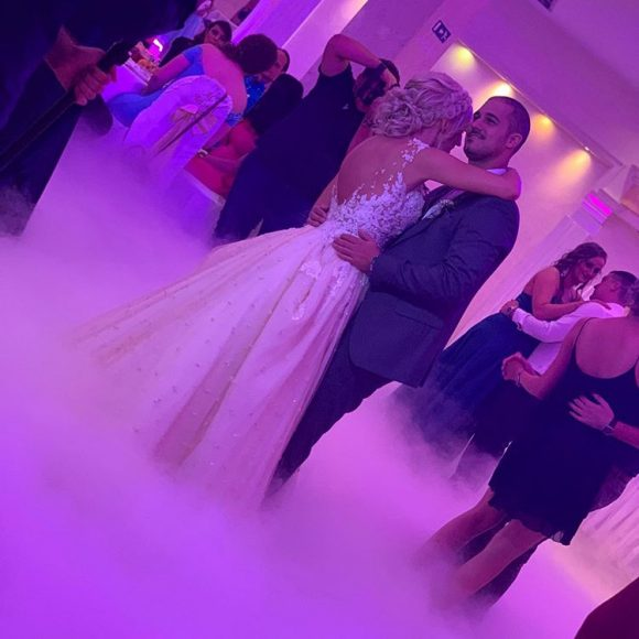 Mlada i mladoženja plešu šrvi ples po teš ledakom dimu od suvog