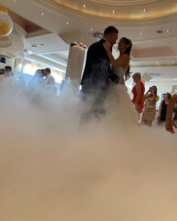 Mlada i mladoženja na venčanju plešu prvi ples uz teški dim od suvog leda