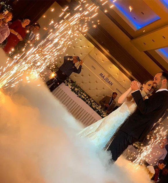 Mlada i mladoženja plešu uz prvi ples sa teškim dimom od suvog leda