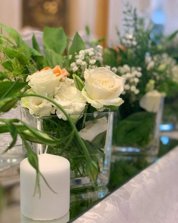 Dekoracija sa belim cvećem i svećom