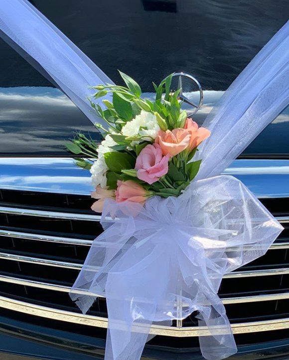 Belo roze cvetni aranžman na automobilu