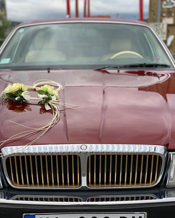 Srce od pruća i belog cveća sa ružama na automobilu
