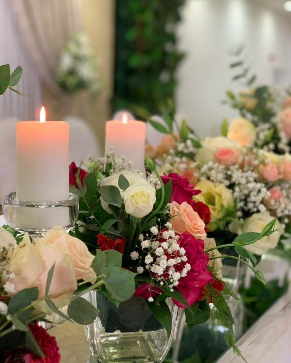 Dekoracija mladenačkog stola sa svećama i cvećem