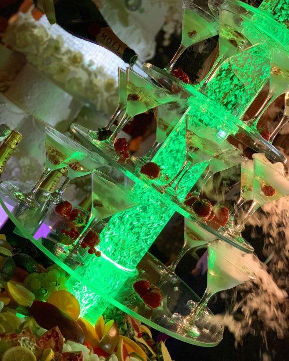 Sampanjac fontana sa čašama dekorisano voćem i sa suvim ledom