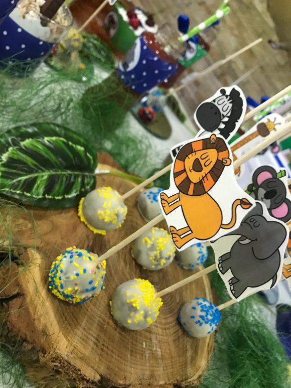 Loli pops sa likovima iz dzungle na panju i mahovini na slatkom stolu