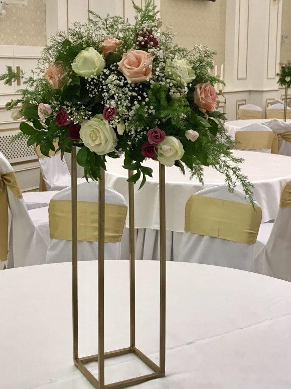 Cvetni aranžman na stolu sa belim i roze ružama na zlatnom postolju