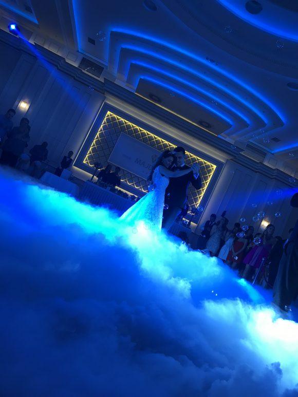 Mladenci plešu prvi ples na dimu od suvog leda