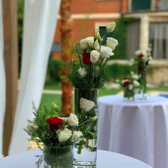 Vaze sa belim i crvenim ružama dekorisanu aranžmani po stolovima