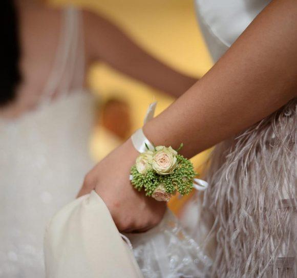 Mlada sa roze cvetićem za venčanje na ruci