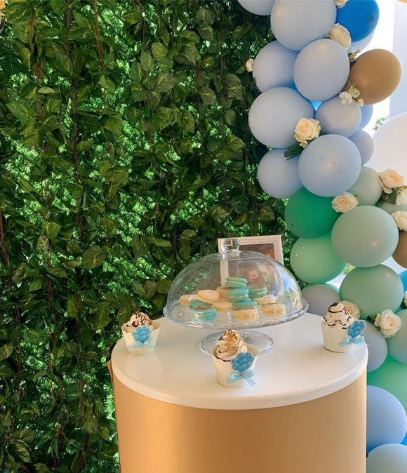 Slatki sto na buretu za dekoracija rodjendana sa balonom i zelenom pozadinom